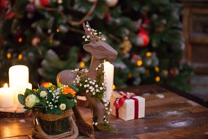 Christmas composition with figure of deer decorated for new year on dark wooden background. Festive mood