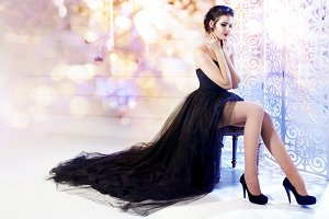 Beauty Brunette model woman holiday make up. Elegant girl in a black dress with very long train