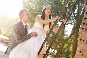 Groom and bride climbing a ladder