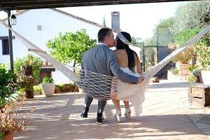 Groom bride kissing in hammock ropE