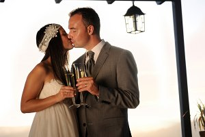 Groom and bride kissing and toasting