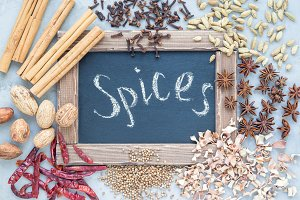 Different kinds of aromatic winter spices around chalk board on gray concrete background, top view, horizontal