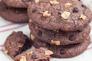 Homemade chocolate cookies with walnuts and chocolate chips on table, vertical