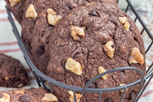 Homemade chocolate cookies with walnuts and chocolate chips in metal basket, vertical