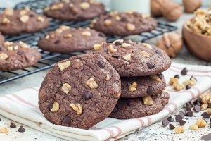 Homemade chocolate cookies with walnuts and chocolate chips on table and cooling rack, horizontal