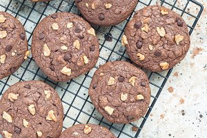 Homemade chocolate cookies with walnuts and chocolate chips on cooling rack, vertical, top view, copy space