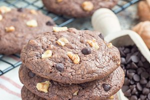 Homemade chocolate cookies with walnuts and chocolate chips on table and cooling rack, vertical