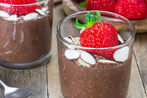Chocolate chia seed pudding garnished with almond slices and strawberry, square format