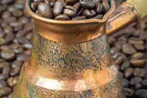 Coffee beans in copper cezve, close up