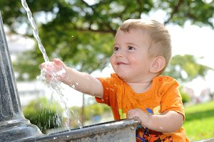 Blonde boy playing with water