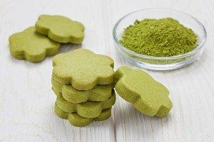 Homemade matcha green tea shortbread cookies on wooden table