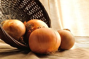 Onions out of a basket on a table