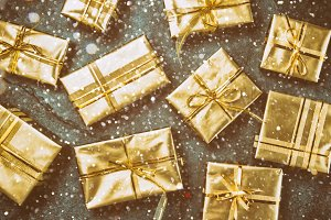 Christmas background. Golden gift boxes on slate background. Flat lay, top view