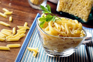 Uncooked macaroni in a glass bowl