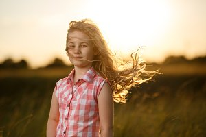 Little blonde child girl standing in summer field at sunset.