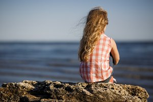 Little girl sits on a rocky shore and looks at the sea.