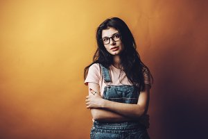 Portrait of smart beautiful brunette girl in eyeglasses with natural make-up, on yellow background.