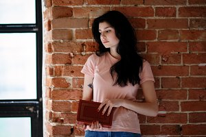Beautiful brunette young woman with book standing near brick wall.