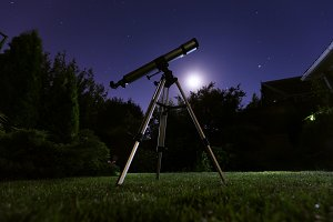 A telescope standing at backyard with night sky in the background. Astronomy and stars observing concept.