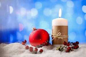 Candle and christmas decoration in snow with blue light background.