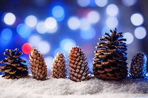 Snowy christmas background with fir and pine cones.