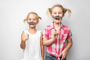 Two cute little girls with paper mustaches while posing against