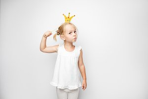 Beautiful little girl with paper crown posing on white background at home.