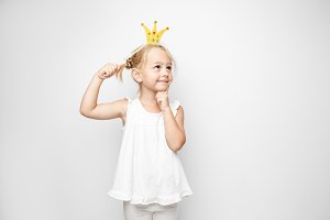 Beautiful little girl with paper crown posing on white backgroun