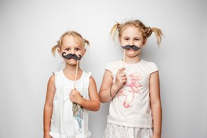 Two cute little girls with paper mustaches while posing against white background.