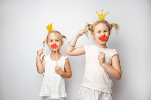 Two cute little girls with paper crown and red lips posing white
