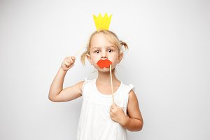 Beautiful little girl with paper crown and red lips posing on white background at home.
