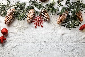 Snowy christmas background with fir branch and pine cones.
