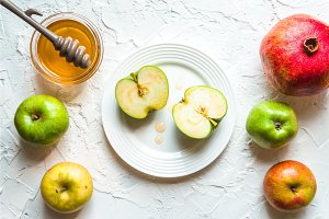 Holiday Rosh Hashanah, fruits and honey on a white table