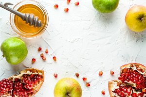 Frame of pomegranate, pomegranate seeds and apples with honey for the Rosh Hashanah