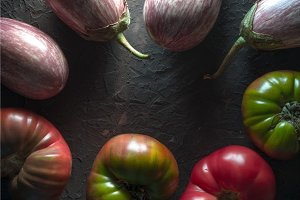 Frame of multi-colored tomatoes and aubergine on a gray table