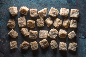 Background of cubes of cane sugar on a gray stone line