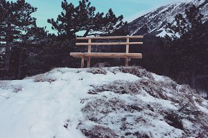 Wodden bench in winter mountains
