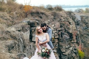 Groom tenderly embracing her beautiful bride by behind. Autumn wedding ceremony in rustic style outdoors. Newlyweds are posing on mountains background