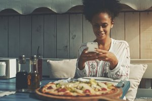 Black girl taking picture of pizza
