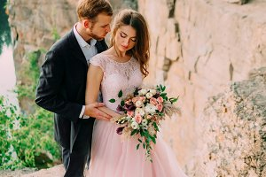 Happy newlyweds embracing. Man in tuxedo and woman in a pink wedding dress is posing on nature. A ceremony outdoors. Close-up