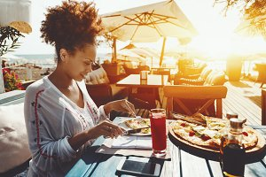 Woman in cafe eating fresh pizza