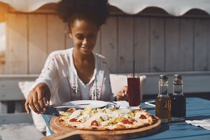Black girl taking piece of pizza