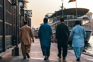 Four Men Walking Next To Canal