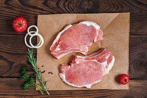 Fresh raw pork steaks on a craft paper on wooden background