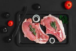 Raw fresh pork steaks on a black baking sheet on black background, concept of flat black color