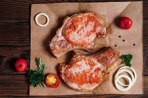 baked pork steaks on a craft paper on wooden background