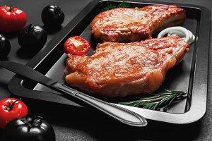 Baked pork steaks on a black baking sheet on black background, concept of flat black color