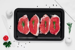 Raw fresh pork steaks on a baking sheet on white background