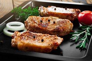 Baked pork steaks on a black baking sheet on wooden background