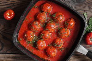 Meatballs with spicy tomato sauce in pan. on wooden background